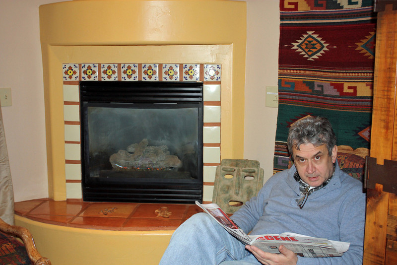 Rustem reading the paper near the kiva fireplace in our room at the Adobe Hacienda. (Sedona, AZ)