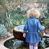Girl in striped tights peering into a fountain.