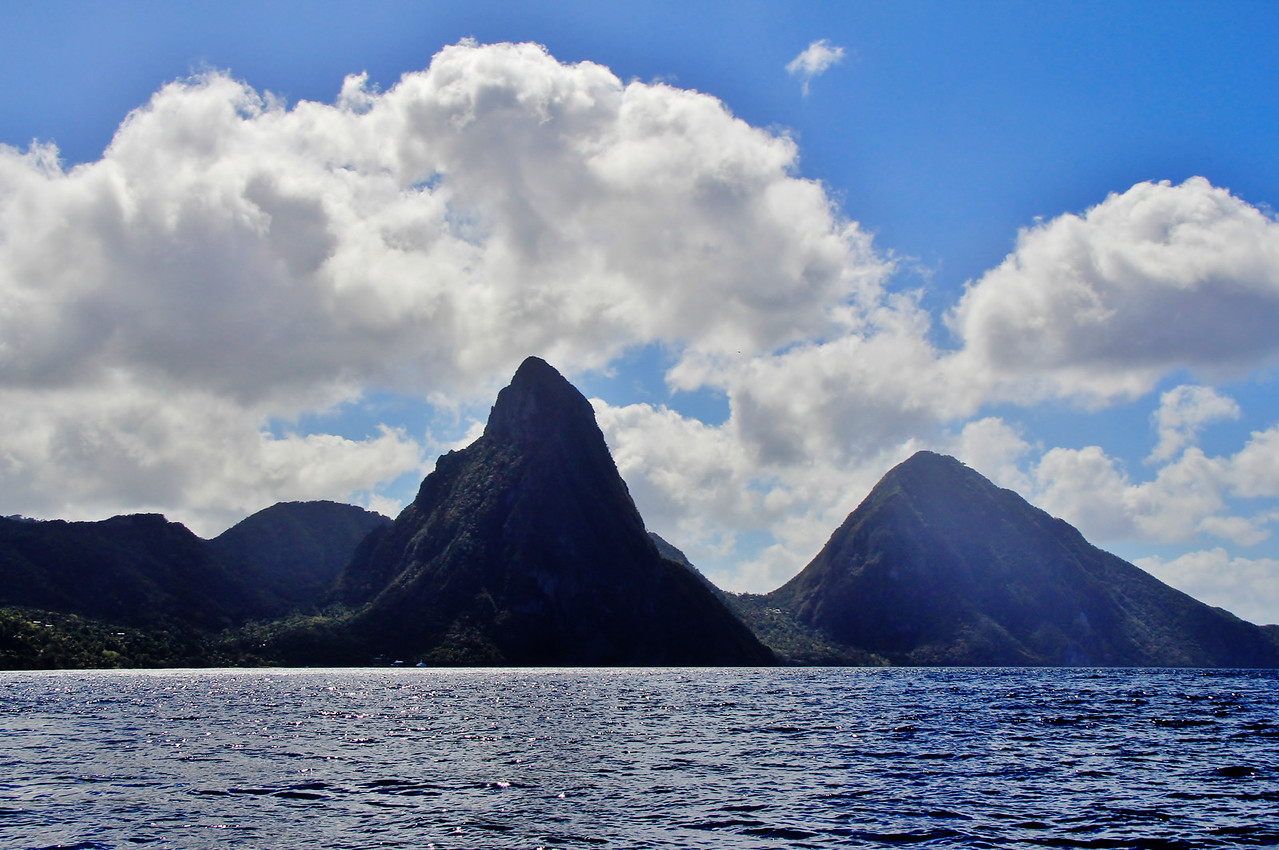 The Pitons are two volcanic plugs in a World Heritage Site in St. Lucia, linked by the Piton Mitan ridge. The two Piton Mountains are the most photographed landmark on the island. The larger of these two volcanic plugs is called the Gros Piton, while the other is the Petit Piton.