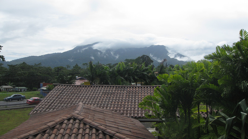 View from Arenal Backpackers Hostel room. Behind those clouds in the Arenal volcano.