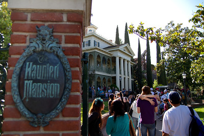 Haunted Mansion Signpost with the Mansion in the background
