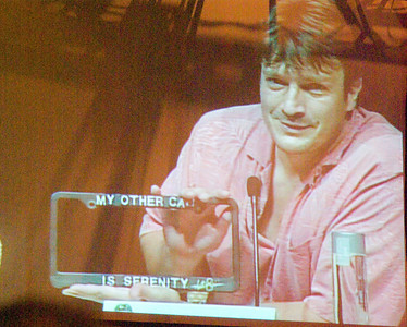 Nathan Fillion and his very own car tag holder he gave away to a trucker in the audience