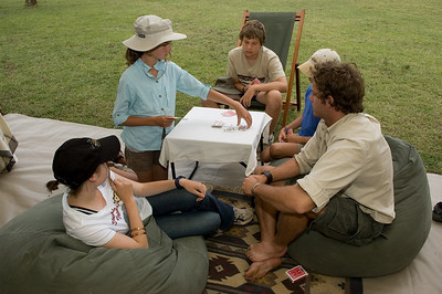 The kids and Tony playing cards in camp