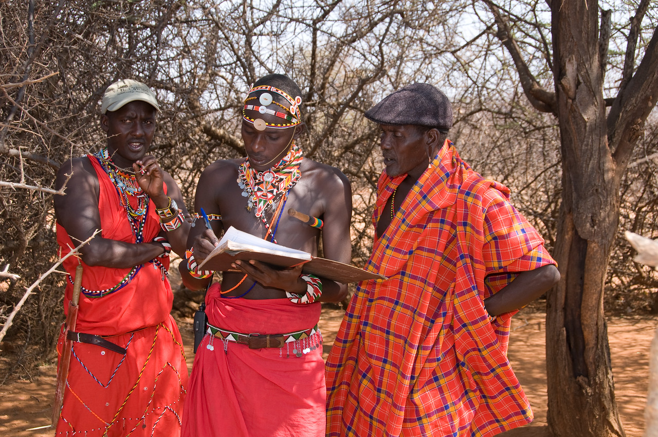 "Dowdy and our other Samburu guide, Winston, ""signing us in"" for the visit with one of the tribe Elders"