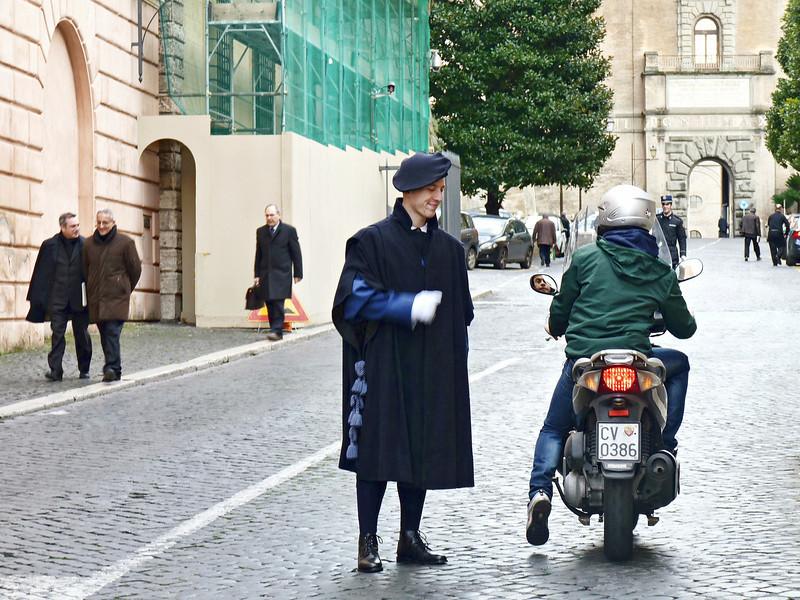 Vatican guard aiding a driver.