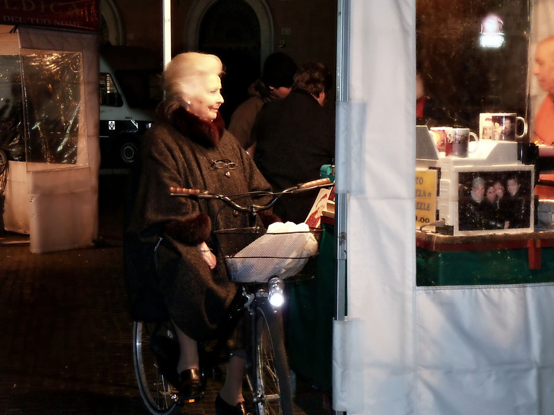 Woman on her bicycle buying sweets from a vendor in Piazza Navona's Festival of the Epiphany.