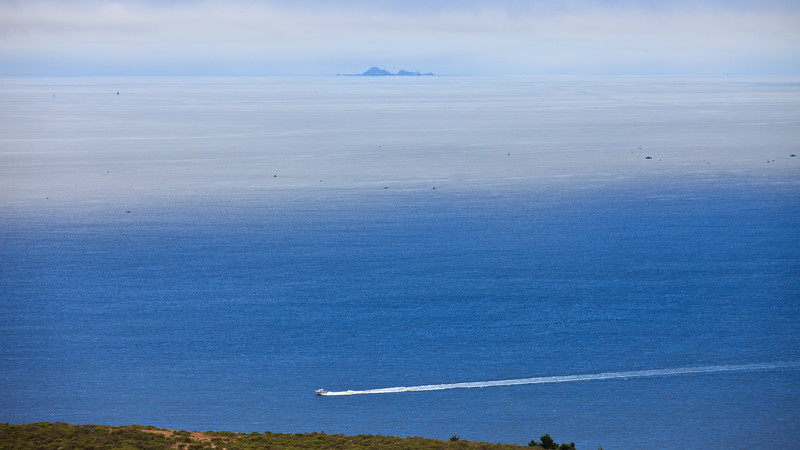 Farallon Islands in the distance fog, one boat running in the sun the others are fishing in the fog