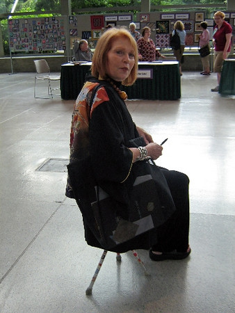 Day 2 Vicki on Horace's tripod stool in the lobby of the Pacific Northwest Quilt Fest