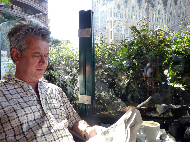 Reading the newspaper in a cafe in the shadows of Gaudi's Sagrada Familia.