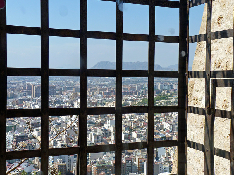 View of Alicante from a dirty window atop Guard tower at the Castillo de Santa Bárbara.
