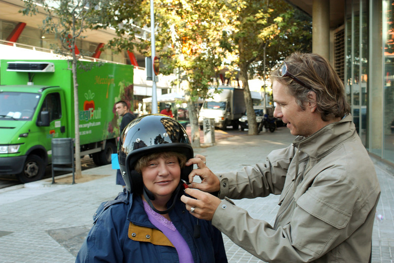 Mattias putting a helmet on Susan as we get ready for our sidecar tour of Barcelona.