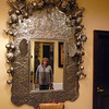 Standing near the hotel's elevator looking into an ornate mirror.