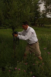 John trying to get his camera ready with my tripod he was hanging it on a little bush