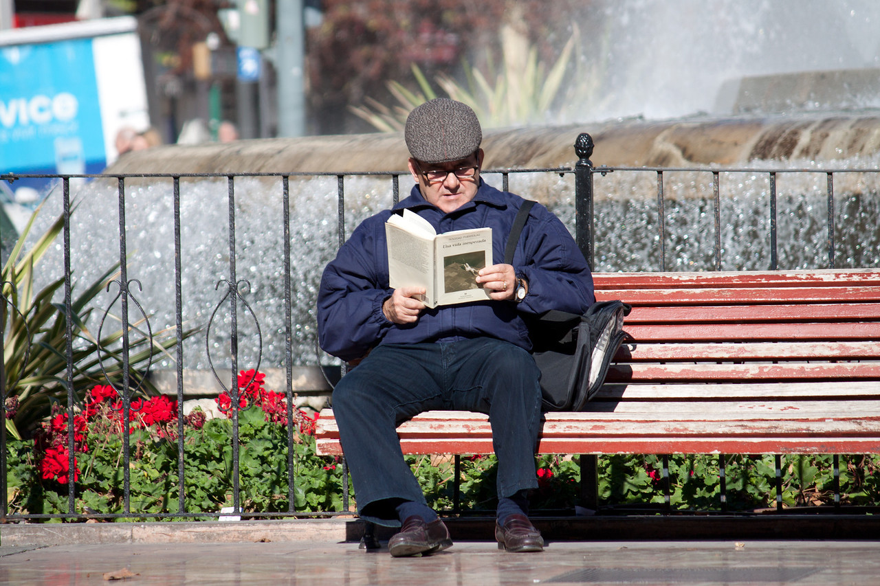 A man reads on a park bench near the city center of Valencia, Spain on Janurary 27, 2014.
