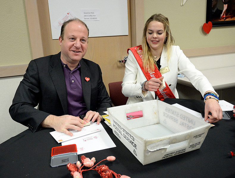 Gov. Jared Polis, left, and Miss Loveland Valentine 2019 Kat Pfeiffer, right, stamp some of the first valentines Monday, Feb. 4, 2019, to kick off the first day of stamping for the 2019 Loveland Valentine Remailing Program at the Loveland Chamber of Commerce in east Loveland.    (Photo by Jenny Sparks/Loveland Reporter-Herald)
