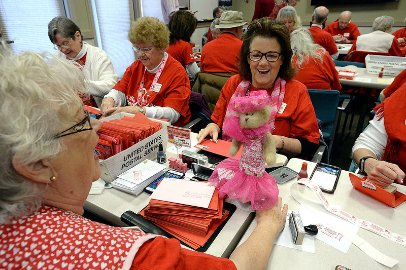 Sisters and volunteer stampers Susie Sermersheim, left, and Debbie Cate, center, show off their bear, Addie Mae Peabody, in her new outift made by Cate for the first day of stamping Monday, Feb. 4, 2019, for the 2019 Loveland Valentine Remailing Program at the Loveland Chamber of Commerce in east Loveland.    (Photo by Jenny Sparks/Loveland Reporter-Herald)