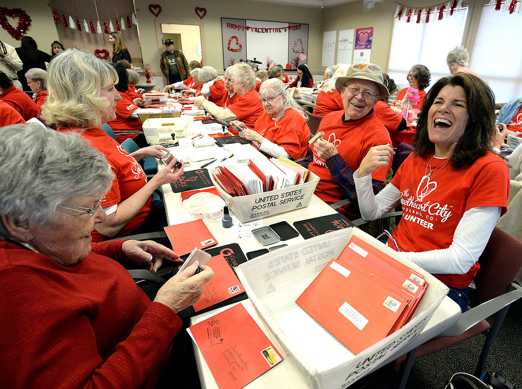 . Valentine stampers share a laugh while stamping cachets on envelopes Monday, Feb. 4, 2019, on the first day of stamping for the 2019 Loveland Valentine Remailing Program at the Loveland Chamber of Commerce in east Loveland. Luanne Martin, far right, and her mother, Evelyn Haber, far left, are full time stampers for the first time this year. Don Spillman, center right, and his sister, Carole Strahm, center, have been stamping together for about seven years. Spillman comes to Loveland for a few weeks from his home in Maryland to stamp with his sister. She stamped with her late husband for over twenty years and her brother started stamping with her when her husband died.   (Photo by Jenny Sparks/Loveland Reporter-Herald)