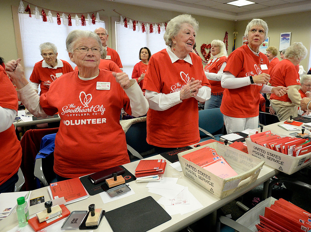 . Volunteer stampers take a short dance break Monday, Feb. 4, 2019, during the first day of stamping for the 2019 Loveland Valentine Remailing Program at the Loveland Chamber of Commerce in east Loveland. From left are Sharon Freihage, Anne Brown, and Edna Pelzmann.   (Photo by Jenny Sparks/Loveland Reporter-Herald)