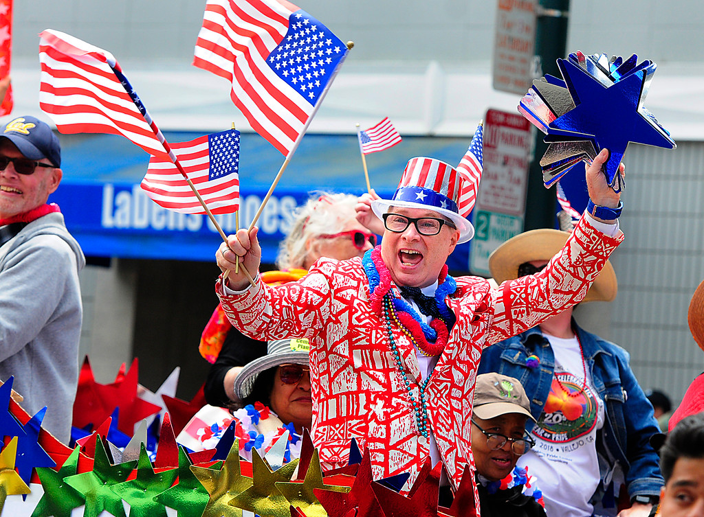 . (Chris Riley/Times-Herald) Brian K. Combs yells as he waves flags and stars around while riding on the Solano Pride float during the 4th of July Parade in Vallejo on Wednesday.