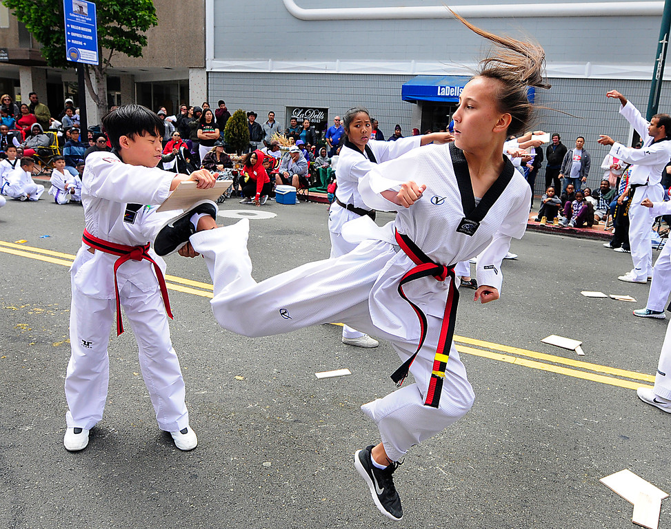 . (Chris Riley/Times-Herald) Kristy Bland breaks a board with a jumping back kick while performing with William Kin\'s Tae Kwon Do Center in the 4th of July parade on Wednesday.