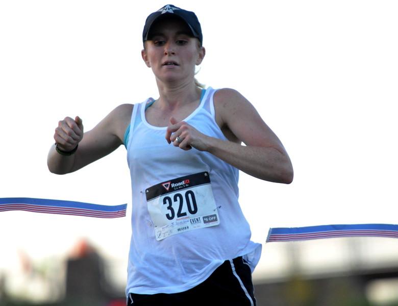 Top female finisher Ericka Joiner crosses the finish-line ribbon to win the Valley 5000 5K on Friday Aug. 19, 2017 at Mehaffey Park. (Cris Tiller / Loveland Reporter-Herald)