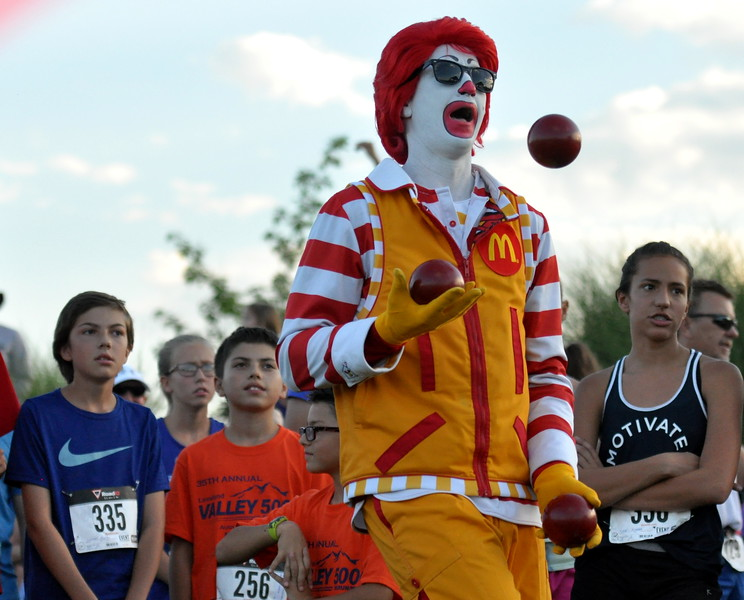Ronald McDonald of the local Ronald McDonald House juggles just before the start of the Valley 5000 5K on Friday Aug. 19, 2017 at Mehaffey Park. (Cris Tiller / Loveland Reporter-Herald)