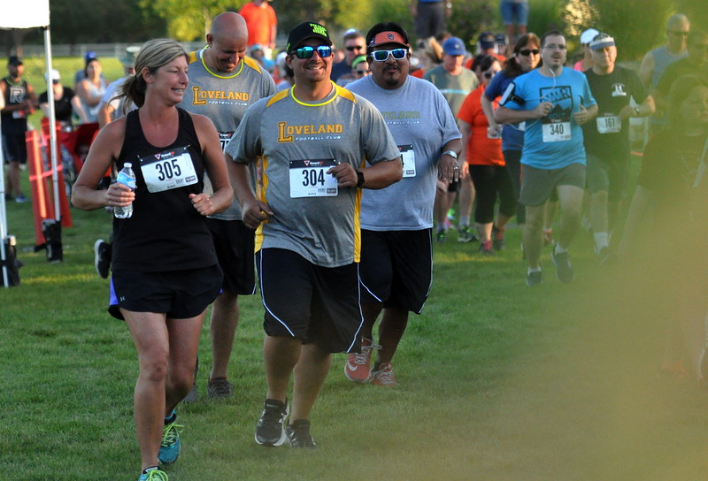 Runners take off the start line of the Valley 5000 5K on Friday Aug. 19, 2017 at Mehaffey Park. (Cris Tiller / Loveland Reporter-Herald)