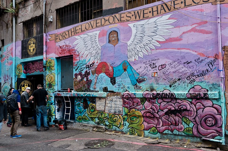 Doorway to the Overdose Prevention Society next to a mural memorializing some  overdose victims