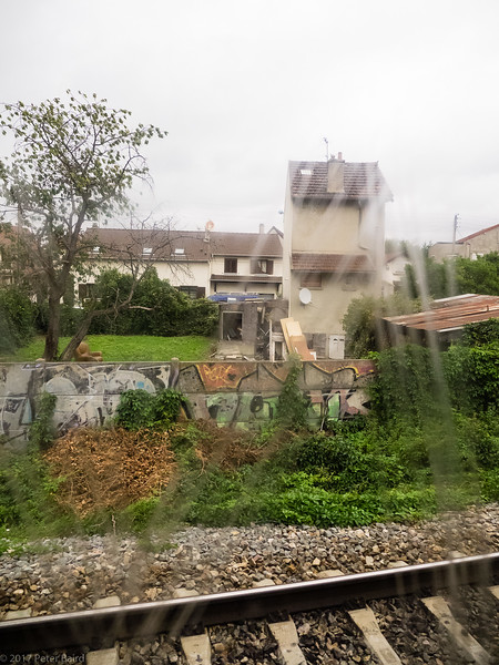 Through scratched windows on the train from the Airport into Paris