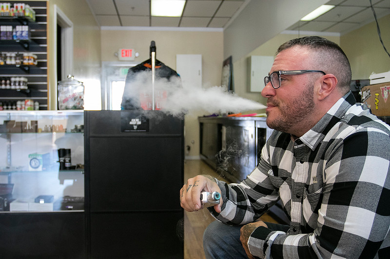 With a federal flavor ban on vaping products looming overhead, businesses like Lineage Vapors, which has several locations in MA and NH, will be significantly impacted. Owner Kyle Ezzio, of Pepperell, does some vaping in his shop in Lunenburg on Friday, September 20, 2019. SENTINEL & ENTERPRISE/JOHN LOVE