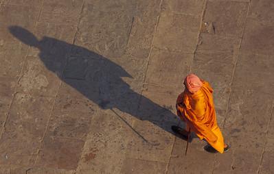 Holy man walking along the banks of the Ganges.  Varanasi, India