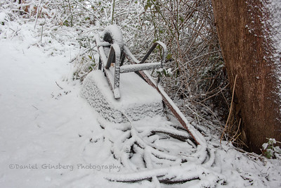 An upside down wheelbarrow and hose covered in snow.