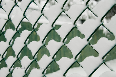 Snow sits on a tennis court chain link fence creating a nice pattern.
