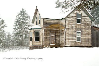 An old wooden house against a back drop of snow.