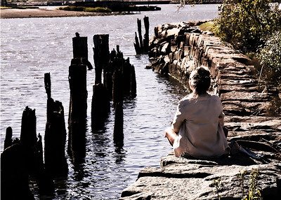 Woman meditating by the river in Rhoad Island.