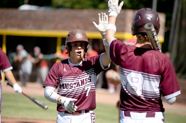 Hayden Fletcher, left, of Monmouth Academy celebrates with Hunter Frost after crossing the plate to put the Mustangs up 1-0 during the first inning of the Class C South regional final against Lisbon High School in Standish.