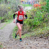 """BELFAST, ME - OCTOBER 23: Cony's Bri Harriman runs up a hill in """"Gollywhoppers"""" section of course during girls Class B cross country North regionals Saturday October 23, 2021 in Belfast. (Staff photo by Joe Phelan/Staff Photographer)"""