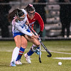 Lewiston's CeCi Miller, left, makes a pass as Messalonskee's Francesca Caccamo bears down on her  during the first half of Tuesday's field hockey playoff game in Lewiston. Photo by Russ Dillingham/Sun Journal