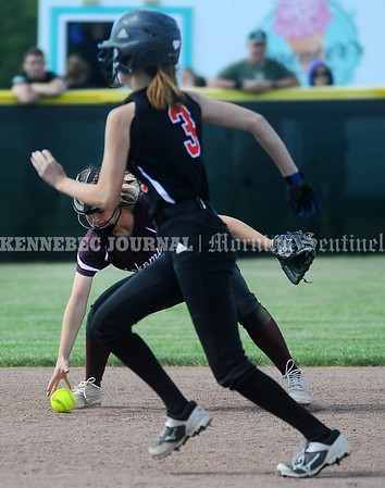 3353# 14494# BREWER, MAINE JUNE 16, 2021.  Winslow runner Nevaeh Dupplessie advances to second base as a Nomomis infielder fields the ball during the Class B North softball championship game in Brewer, Maine Wednesday June 16, 2021.(Rich Abrahamson/Morning Sentinel)