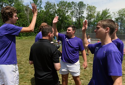 14415# 01tennis HAMPDEN, MAINE JUNE 10 2021. Waterville's Charlie Haberstock, left, and teammate Owen Evans, center, high five as they celebrated with team members after Haberstock won his No.1 singles match over John Baptist's Sean Flynn in Hampden, Maine Thursday June 10, 2021. Also pictured is Waterville coach Jason Tardif, back to camera, and team member Logan Tardif, at right.(Rich Abrahamson/Morning Sentinel)