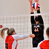 GARDINER, ME - SEPTEMBER 29: Gardiner's Lizzy Gruber jumps up to try and block shot by Cony's Jasmyne Mills  during a volleyball match Wednesday September 29, 2021 in the in the James A. Bragoli Memorial Gym at Gardiner Area High School. (Staff photo by Joe Phelan/Staff Photographer)