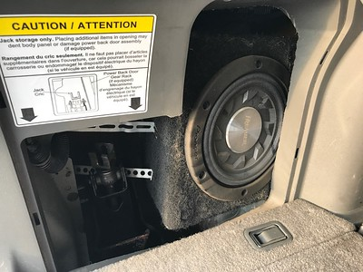 Add subwoofer in left rear fender well, fully covered by access cover for tire jack (shown to left)