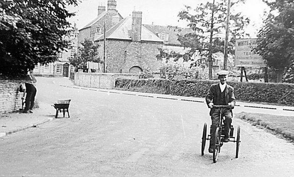<font size=3><u> - Peter Aldridge on Tricycle - </u></font> (BS0214)  William Aldridge rides his tricycle.  (See also BS 0524).  He was the father of Peter, who ran the garage in Crown Square  - see BS 0112.  From evidence of the background, the date would appear c.mid 1950s.  The White Hart sign stood where the entrance to the Library is in 2013 and is located in the hotel's vegetable garden.