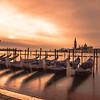 Long exposure shot of gondolas at sunrise with San Giorgio Maggiore Church in the background