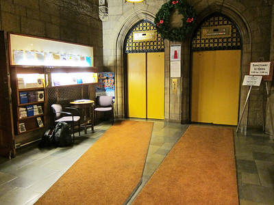 The elevators seen from the outer double doors leading to W. 55th Street. To the right is the receptionist's cubicle; to the left, the double doors leading to the chapel.