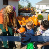 Molly Ocean of Novotny's Farm Market in Vermilion helping Braiden Hicks and his mother Marya Ana select the perfect pumpkin.