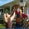 Jennifer Kouth adjusting the flower on her Halloween scarecrow.