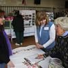 Tammie Streiter, left, listening to Jane Weaver and Margie Fowley at the Raffle Booth.