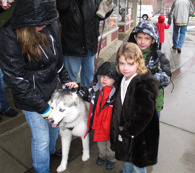 Petting Pepper, a Husky, are Casey, in red, Kylie and Codie Schumack.
