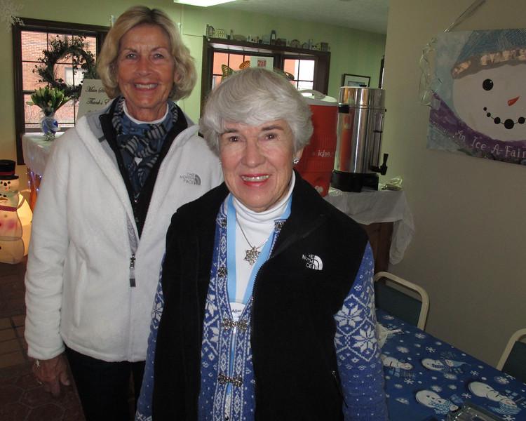 Volunteers Beth Eberhard and Jane Weaver serving hot chocolate and hot cider.